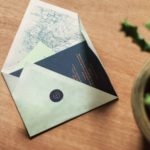 Wedding invitations with copper foil in a folded envelope with a map of Peru